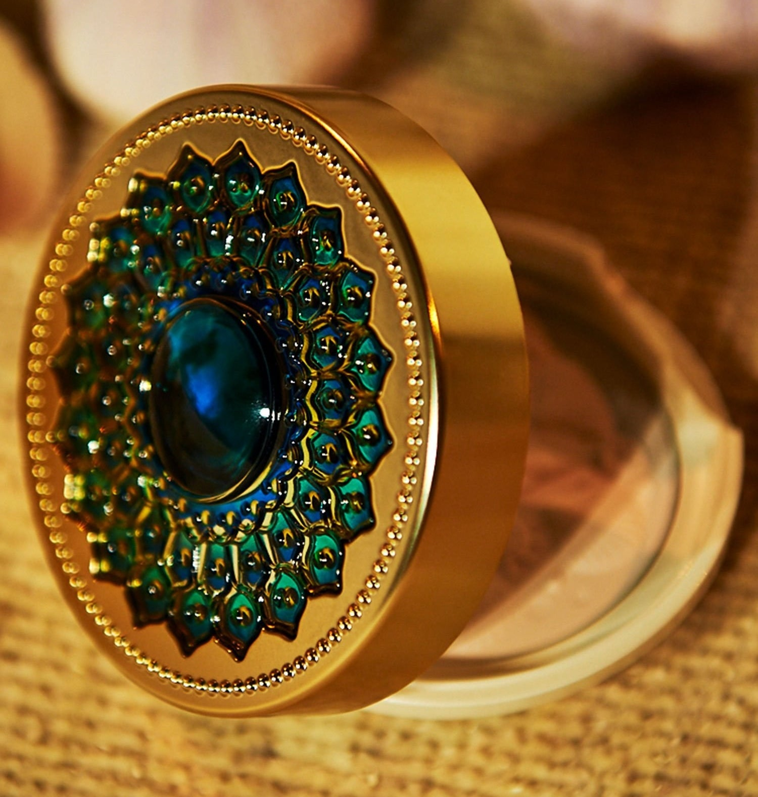 the gold case with a blue jewel in the center