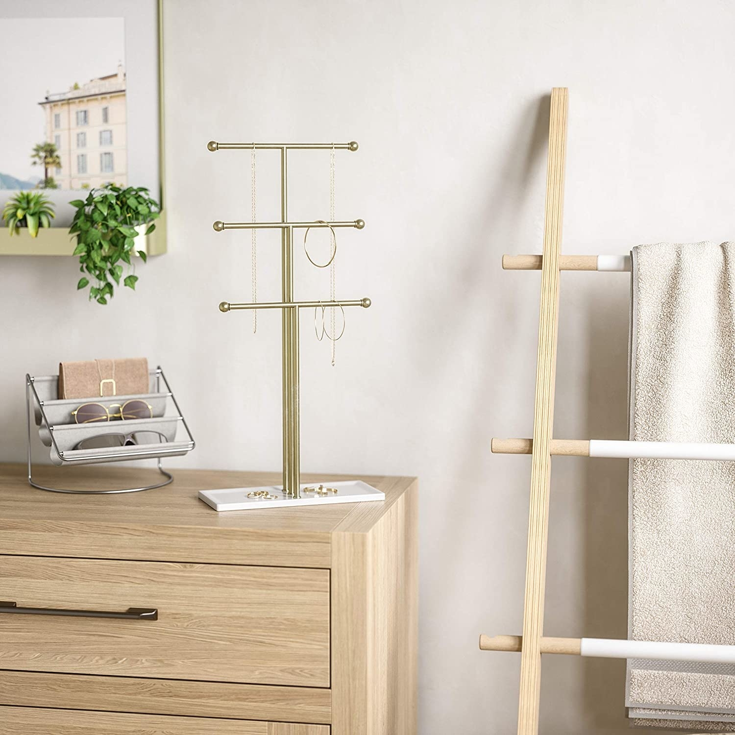 The three-tiered jewelry stand on a dresser