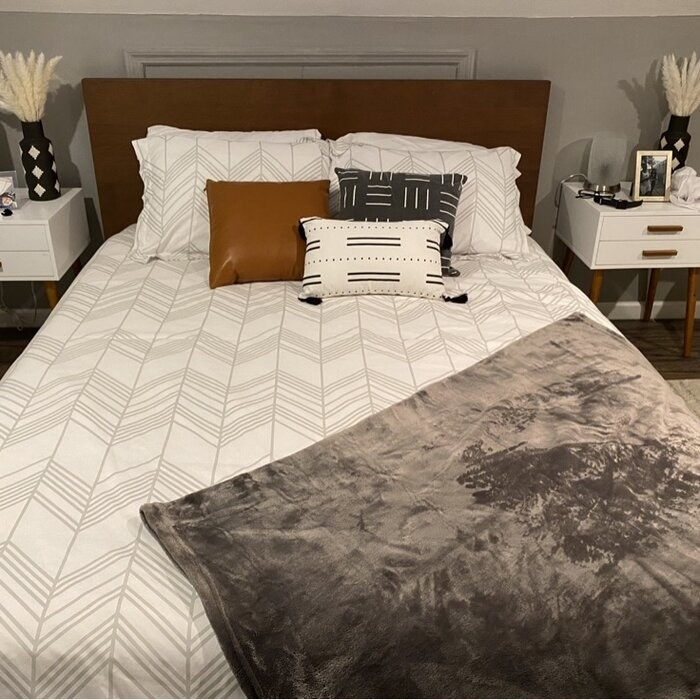 gray and white duvet cover with a blanket and pillows on it