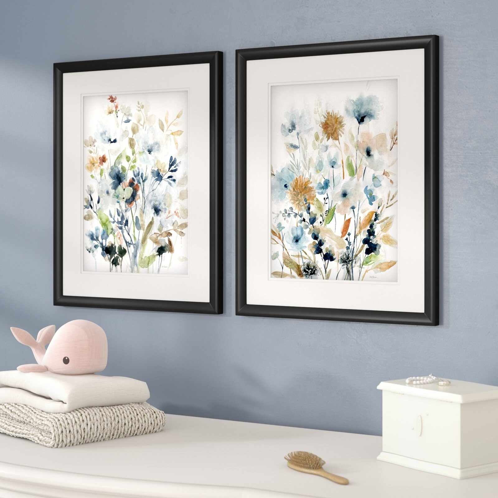 two floral prints in black frames that are hanging on a blue wall