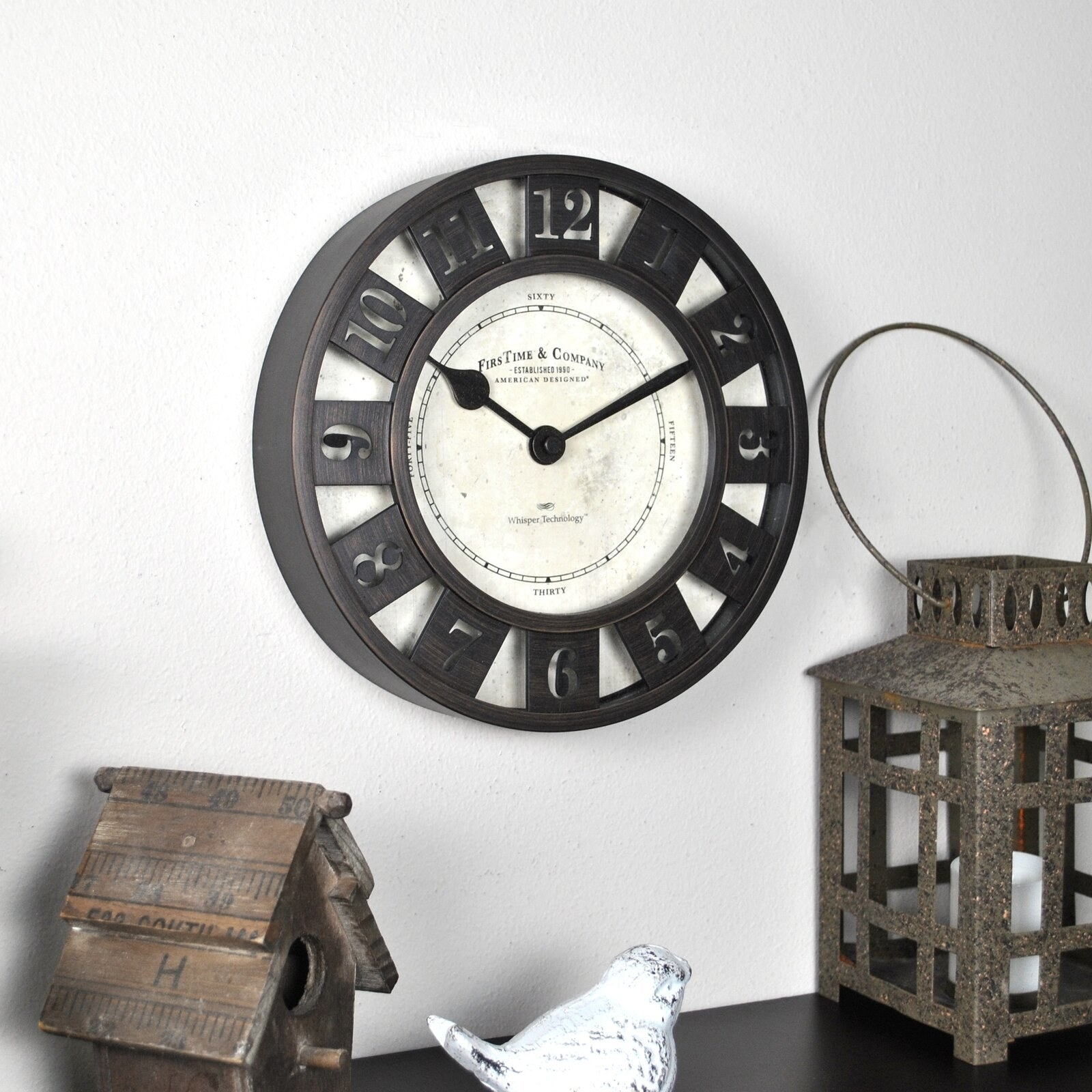 black clock on a wall above decorations