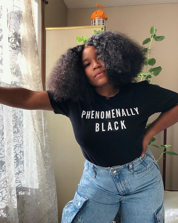 "Model wearing the black short sleeve tee that reads ""Phenomenally Black"" in white letters"