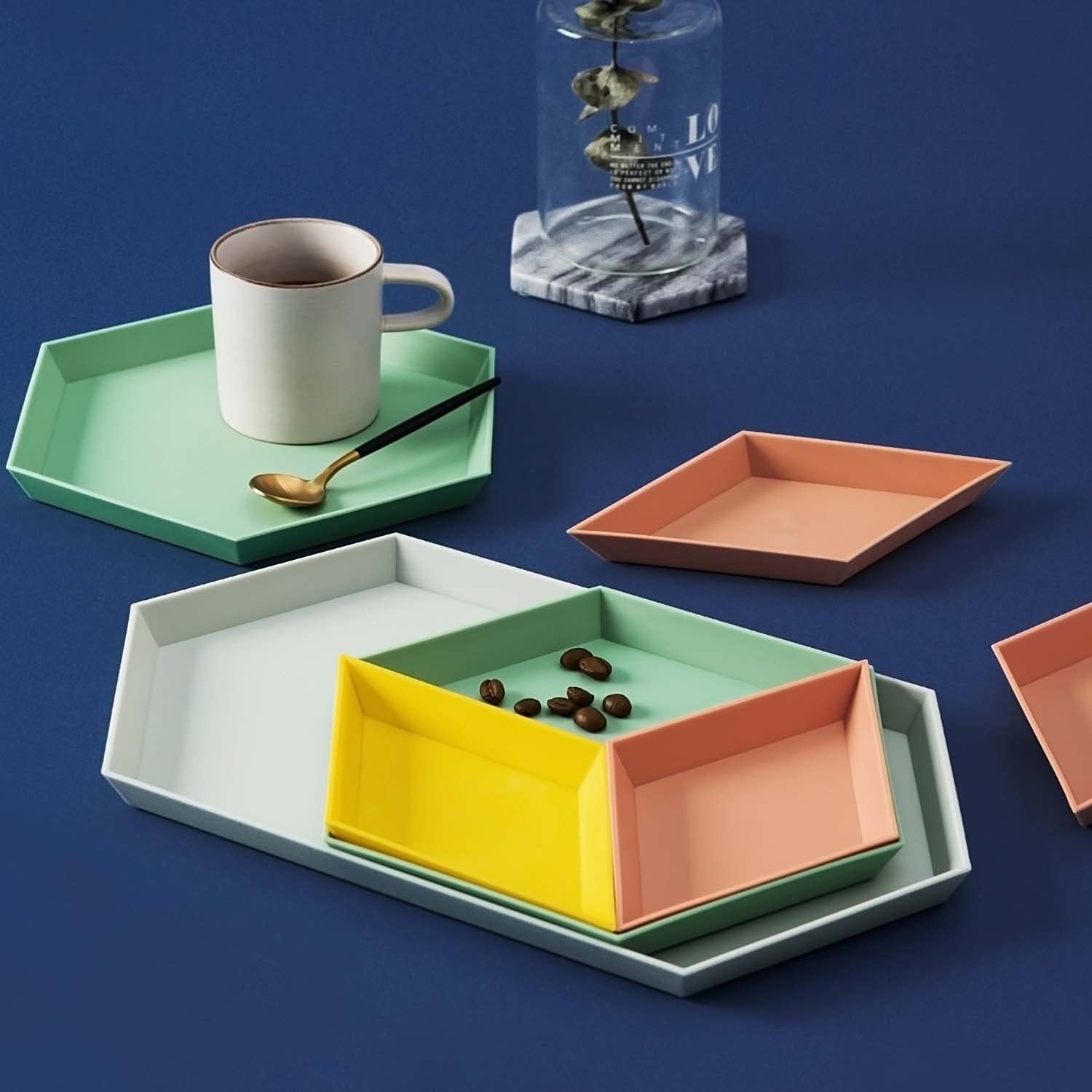 The pastel colored trays stacked and holding a mug of coffee