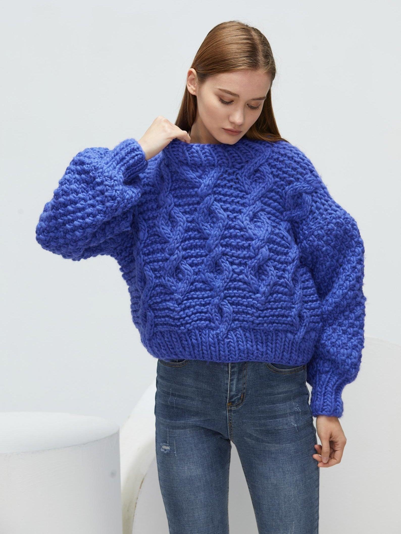 A model wearing the sweater in blue