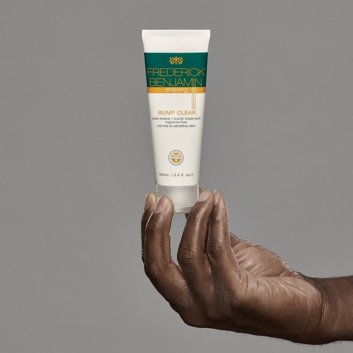 Model holding bottle of Frederick Benjamin Bump Clear post-shave cream