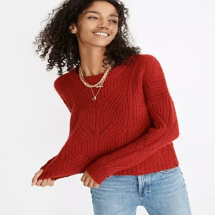 model in red pullover sweater and light blue jeans