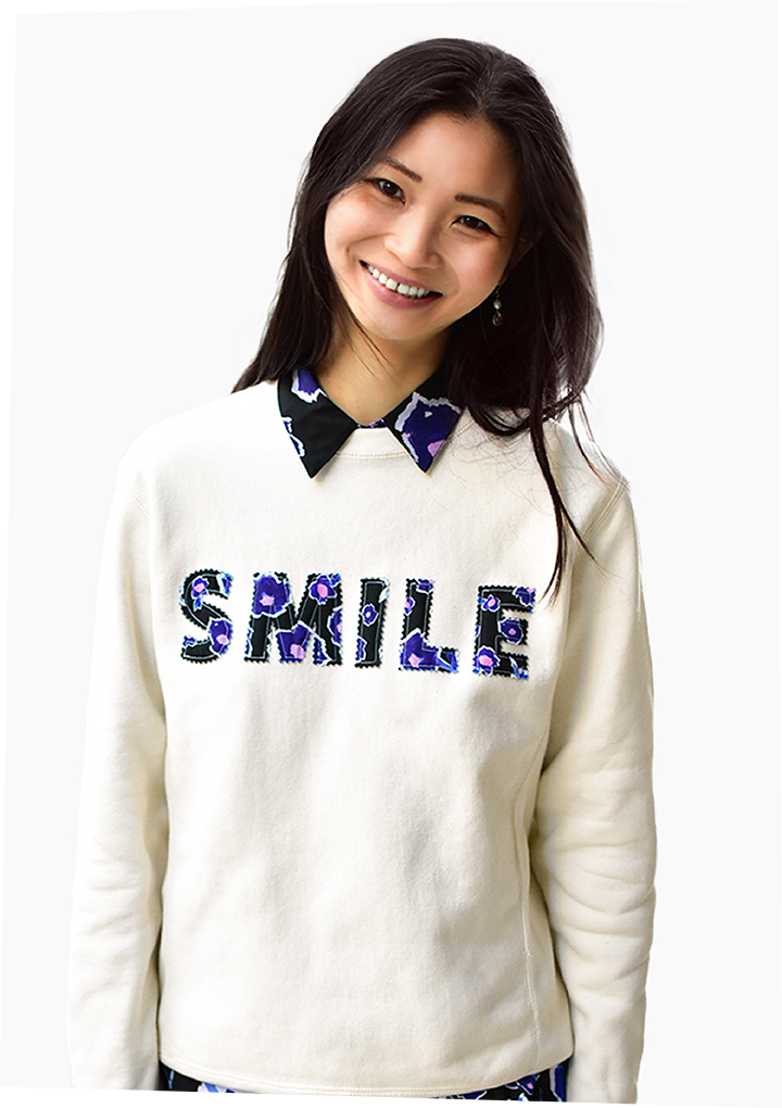 model wearing a white crewneck sweater that says smile