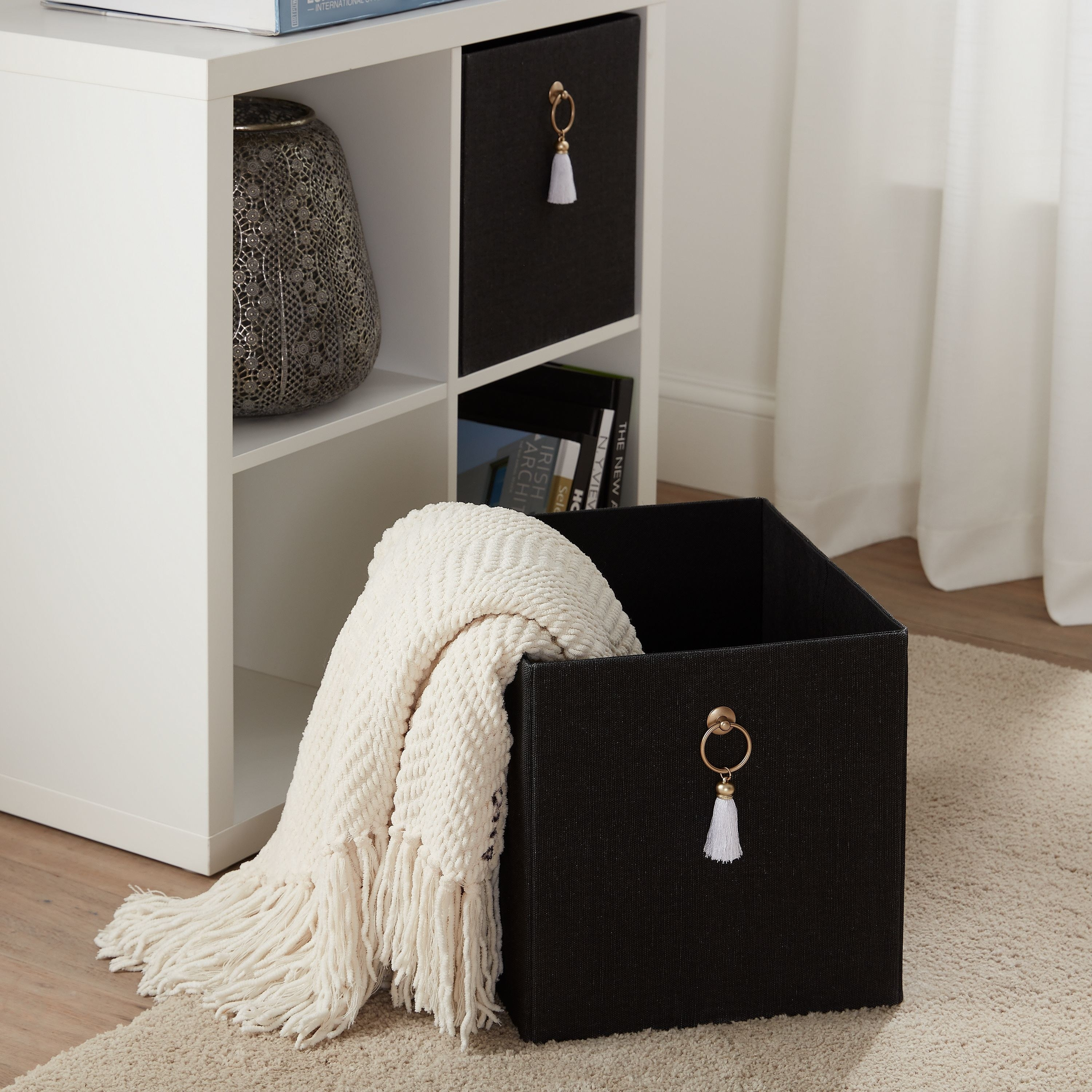 The black, square bin with gold, tasseled ring handles