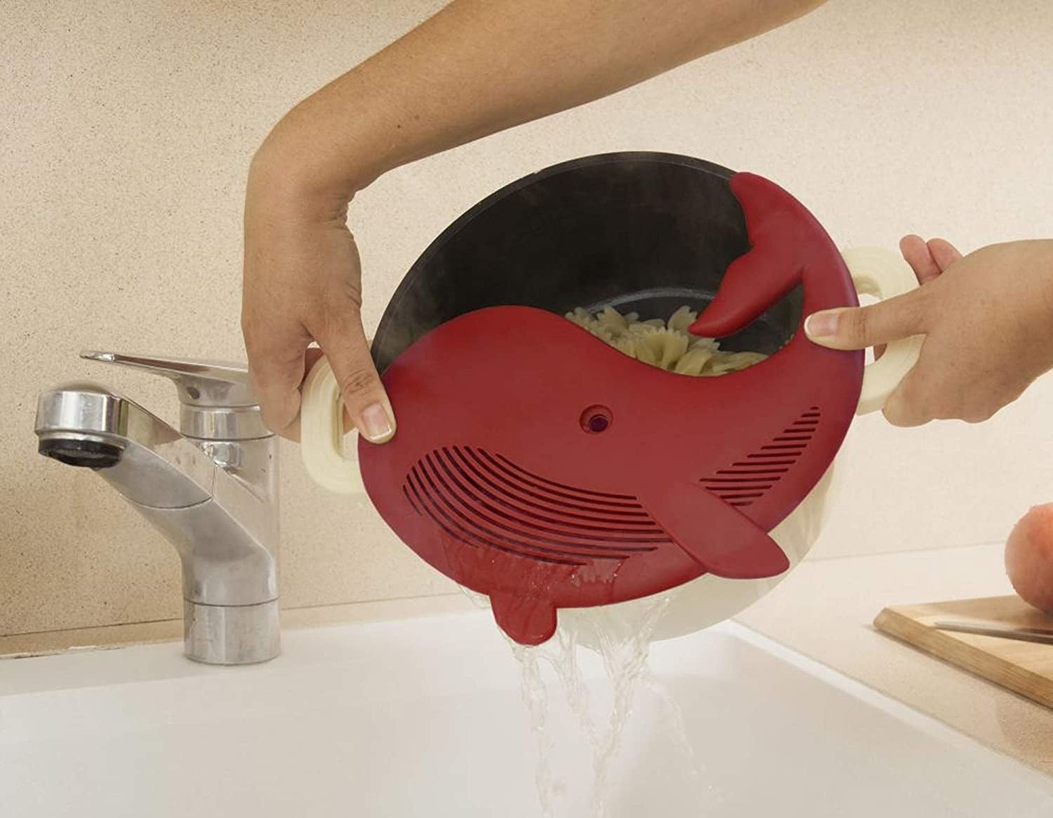 model holding a pot filled with pasta with a red whale-shaped strainer on top, getting the water out of the pot
