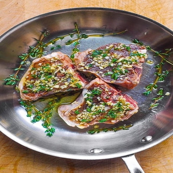 Lamb chops with garlic and herbs in a pan.