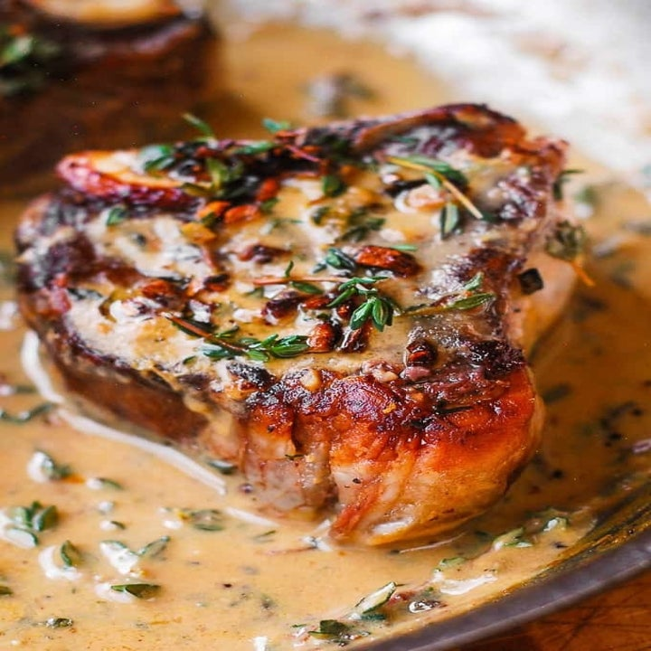 A lamb chop in creamy mustard sauce with herbs.