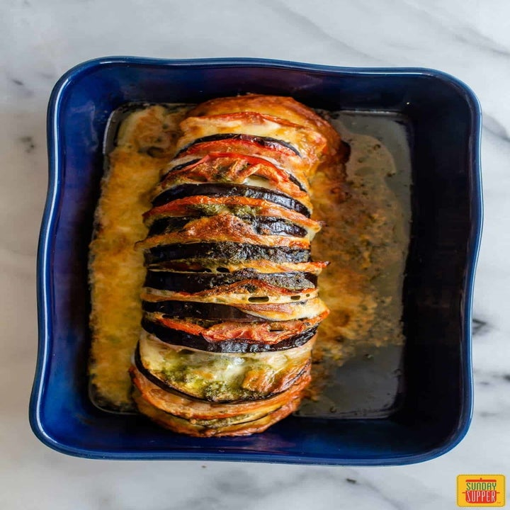 A roasted eggplant stuffed with tomatoes, cheese, and pesto.