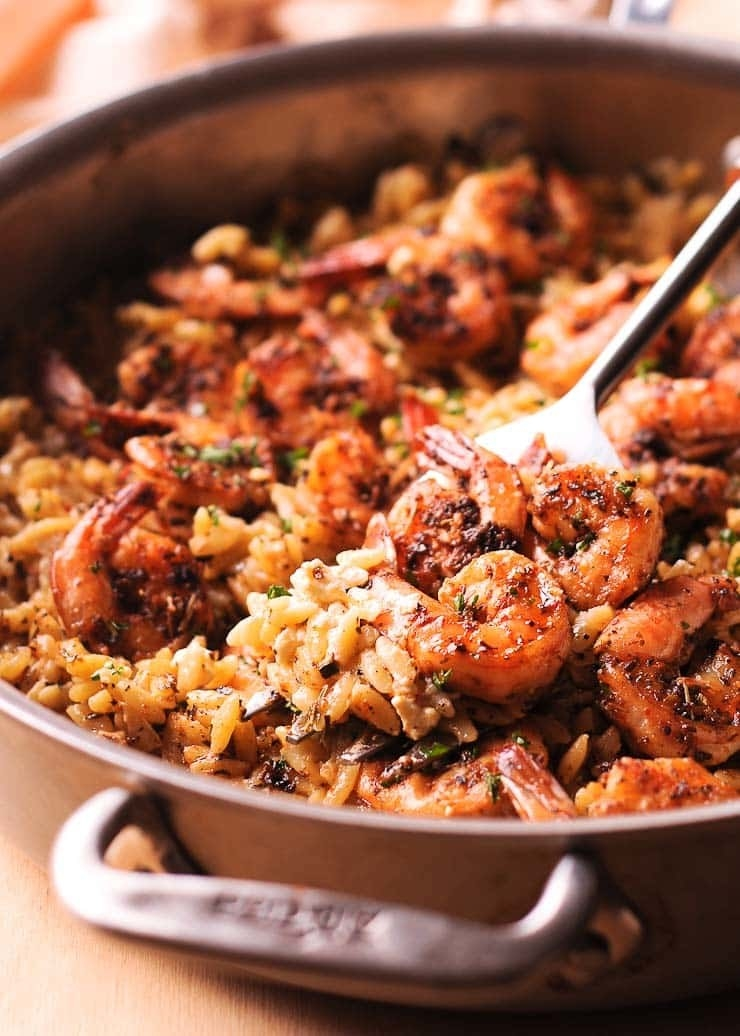 Shrimp and orzo in a pan.