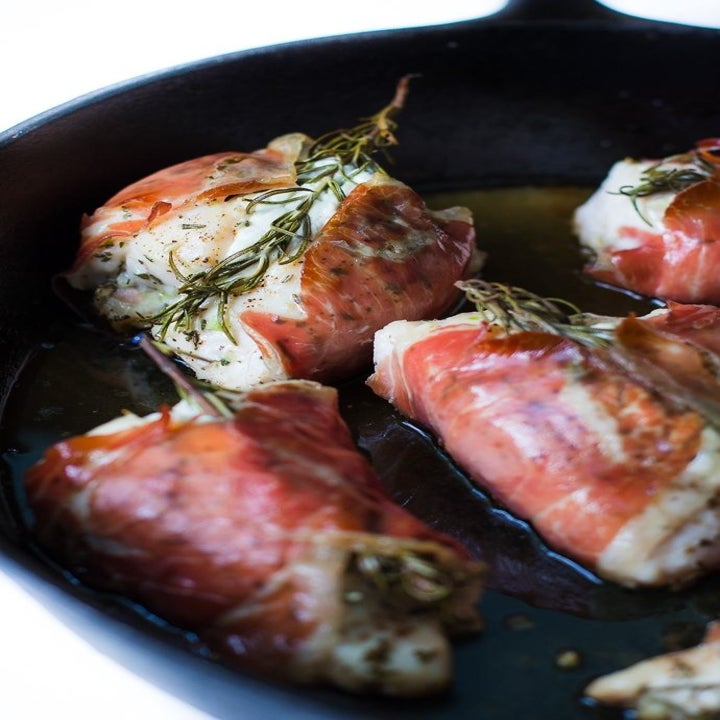Four prosciutto-wrapped chicken breasts in a skillet.