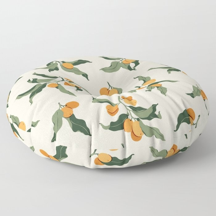 a round floor pillow with kumquats on it