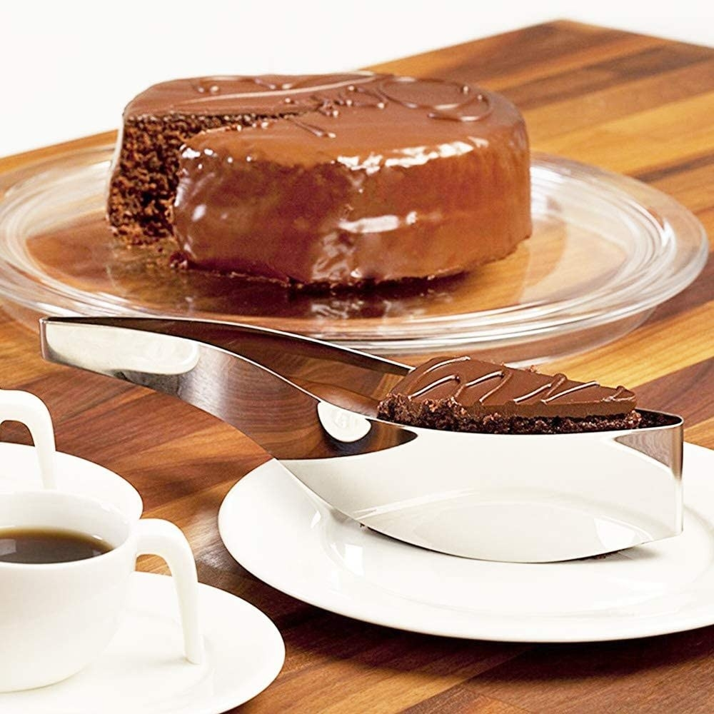 Curved single serve slicer with piece of chocolate cake inside, taken from a full cake in the background