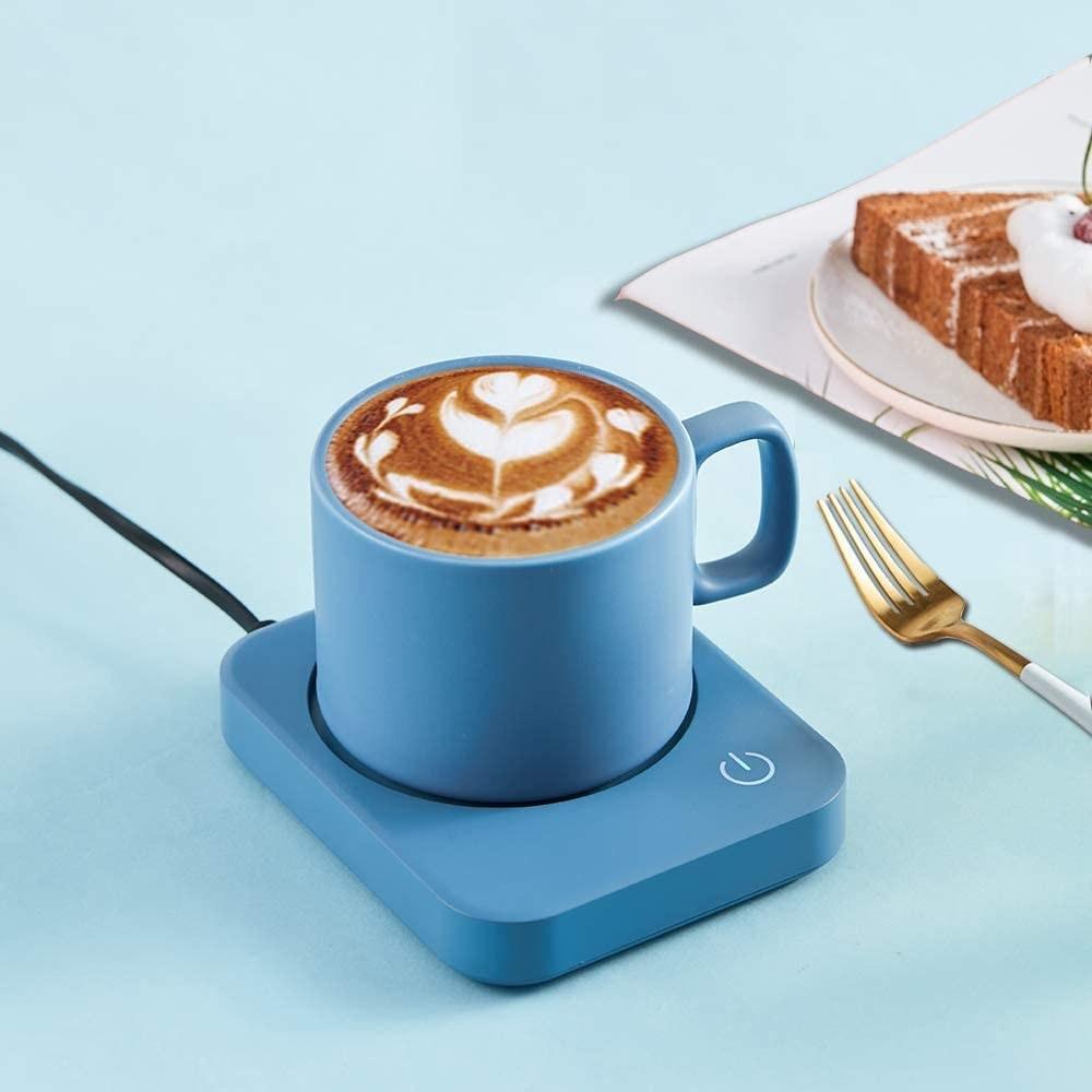 A blue mug warmer on a desk with a mug of coffee on it