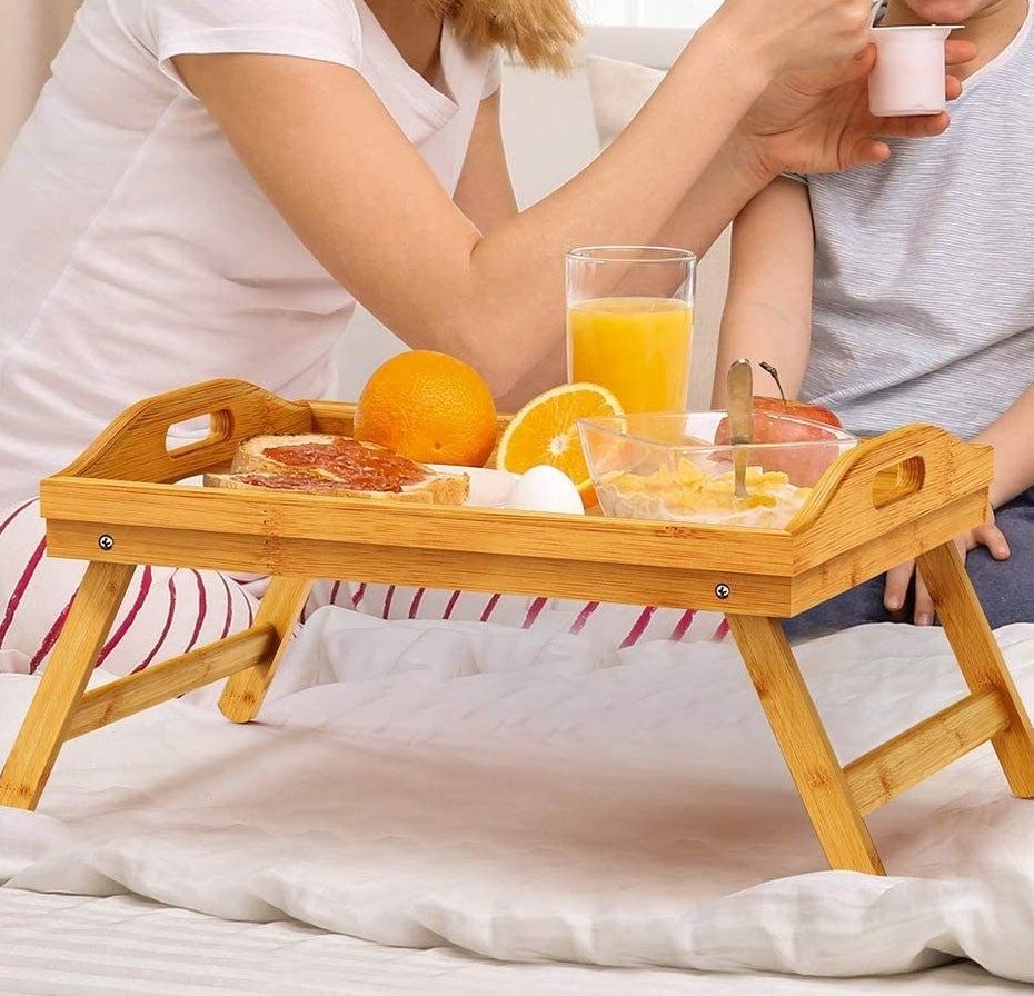 The tray with food and orange juice on it sitting on a bed