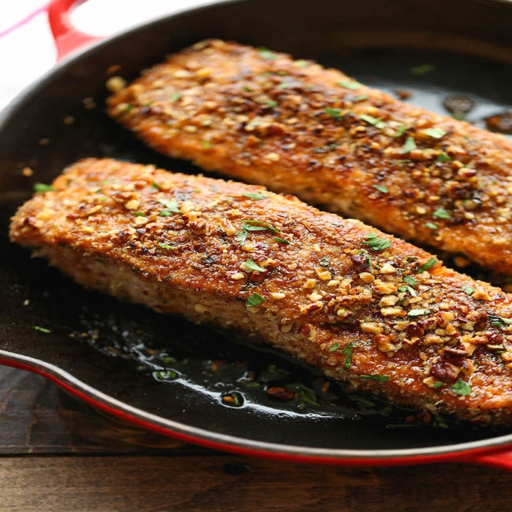 Two pieces of pecan crusted salmon in a skillet.