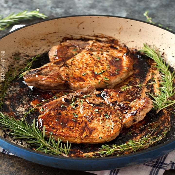 Two glazed pork chops in a pan with herbs.