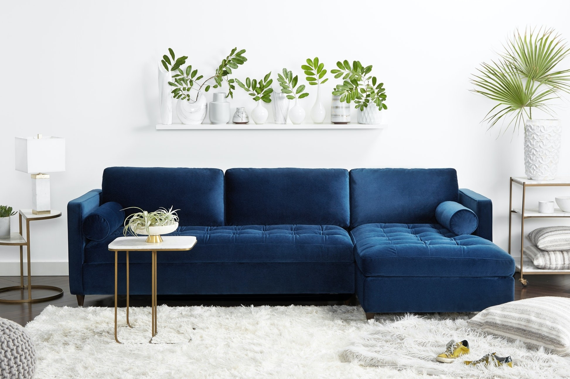 a blue velvet sofa with a chaise