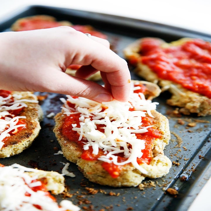 """Putting cheese and marinara sauce on top of cauliflower """"cutlets."""""""