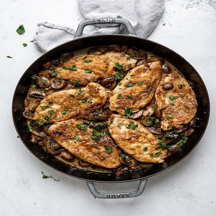A skillet of chicken marsala with mushrooms.
