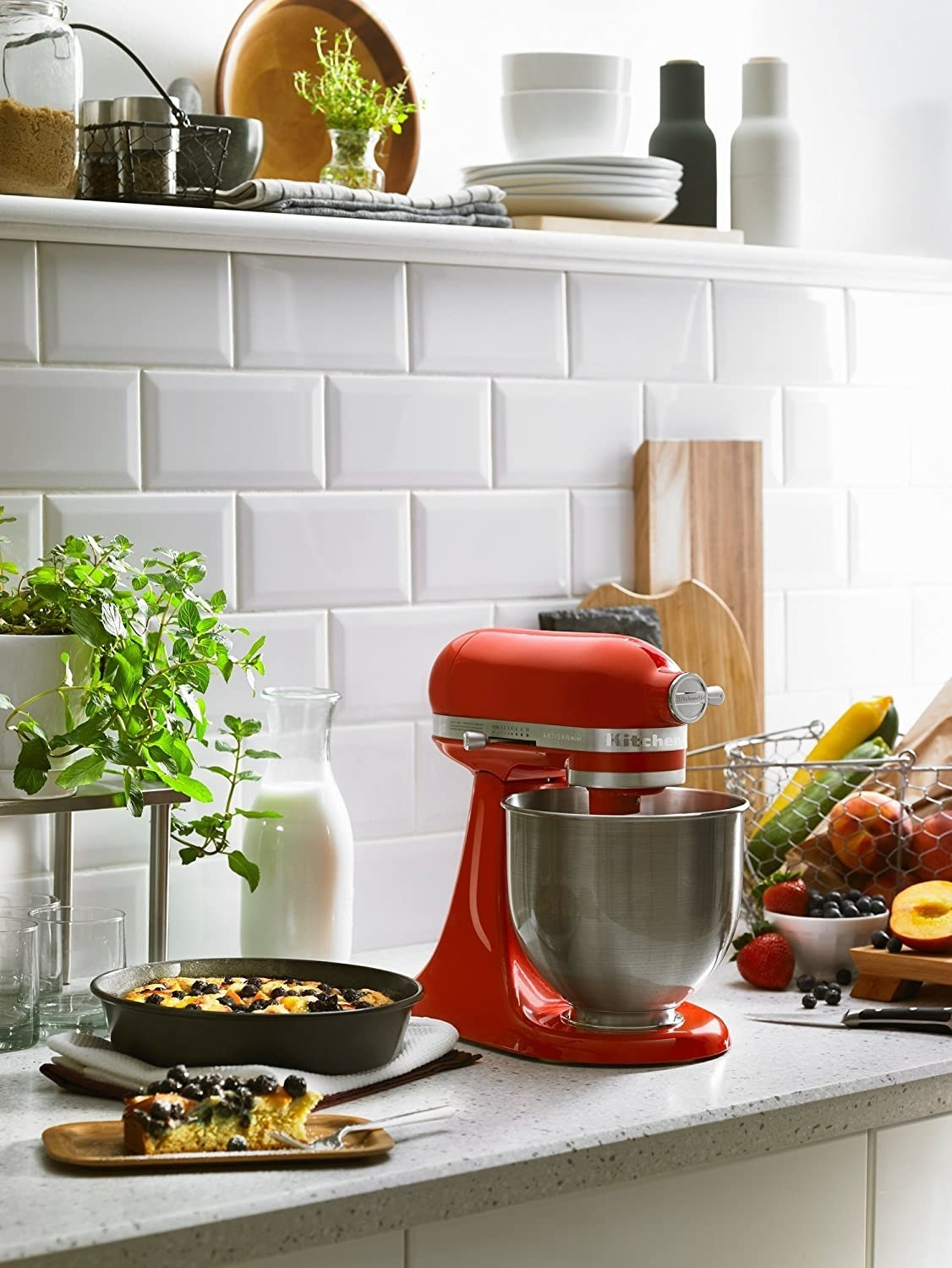 Small stand mixer around vegetables and baked goods