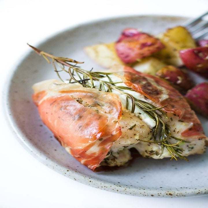 A plate of cheese-stuffed chicken wrapped in proscuitto.