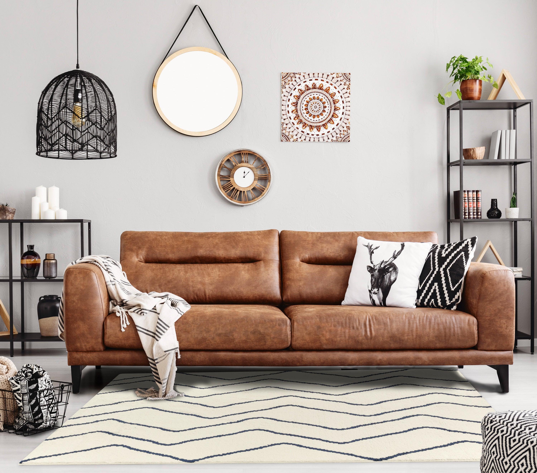 A white rug with black zig-zag stripes