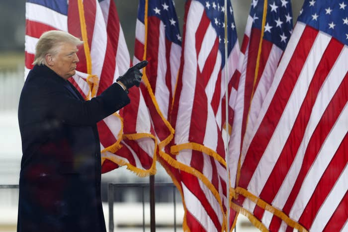 A serious President Trump pointing at an American flag on the stage