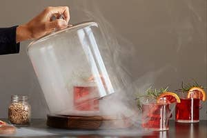 Mixed drink inside glass dome filled with seasoning smoke
