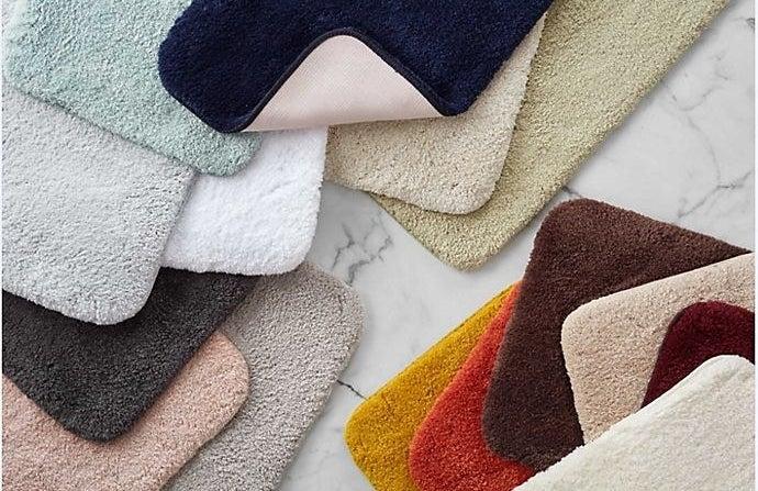 a pile of different colored plush bath mats