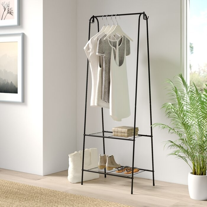 black steel garment rack with clothes hanging up and shoes on the bottom rack