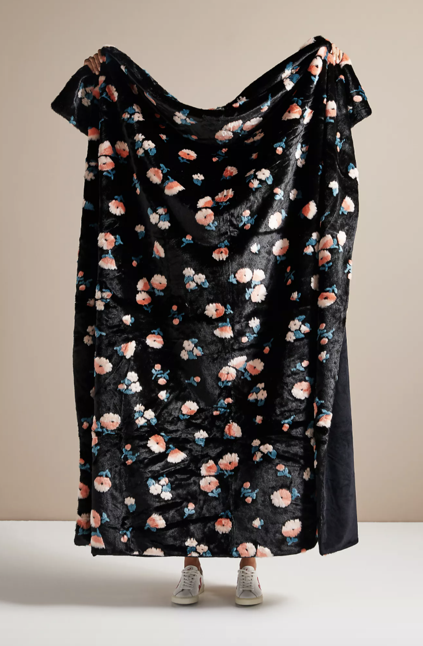 A model holding up a black faux fur blanket with pink flowers on it
