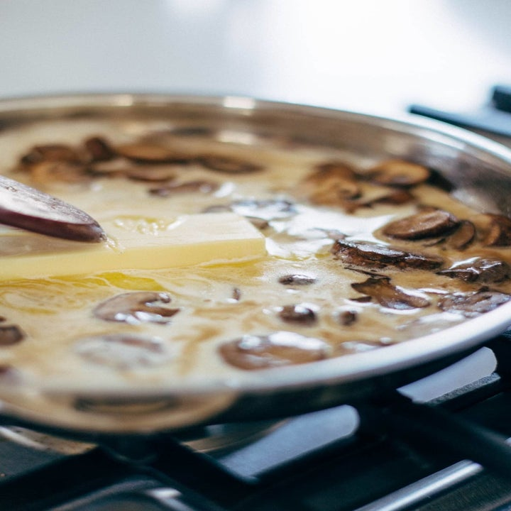 Making alfredo sauce with mushrooms in a skillet.