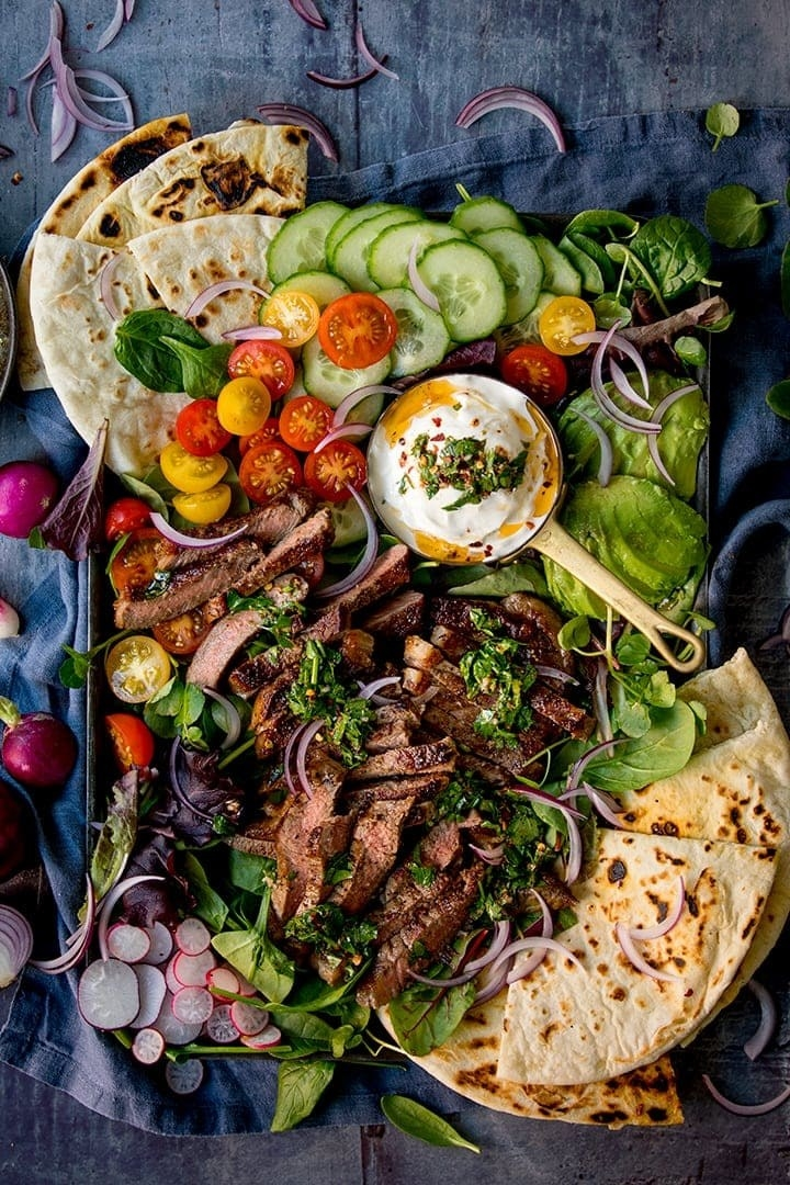 A steak salad with chimichurri sauce, lots of vegetables, and pita bread.