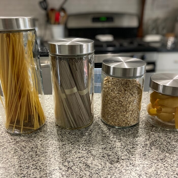 four clear kitchen canisters with ingredients inside of it