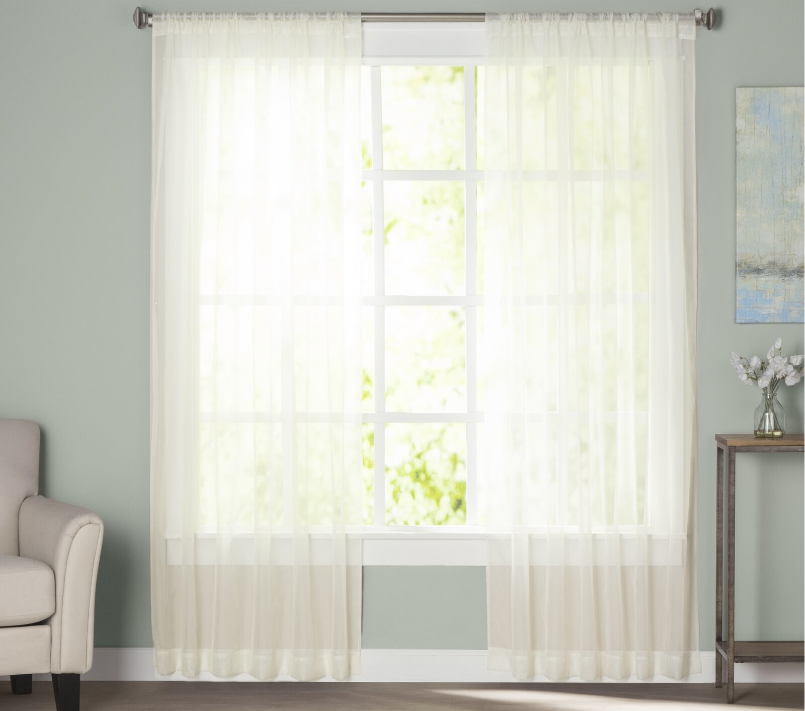 panel of sheer curtains letting light into the room
