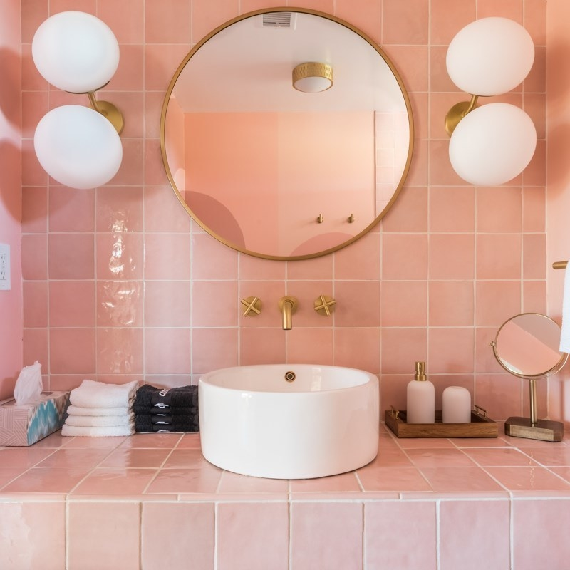 a double bulb wall sconce next to a brass round mirror in a bathroom