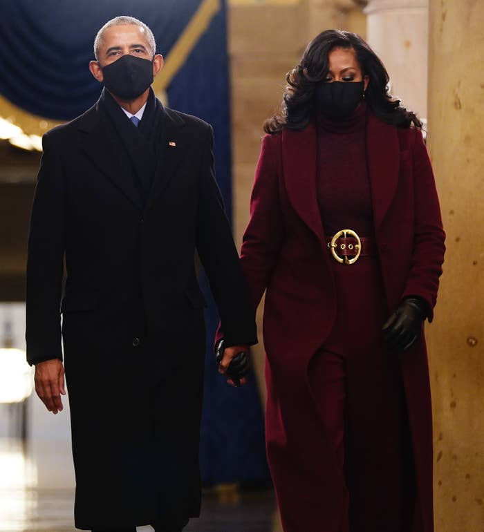 Former US President Barack Obama and Michelle Obama, wearing a matching turtleneck, pants, belt, and long winter coat, arrive for President-elect Joe Biden's inauguration