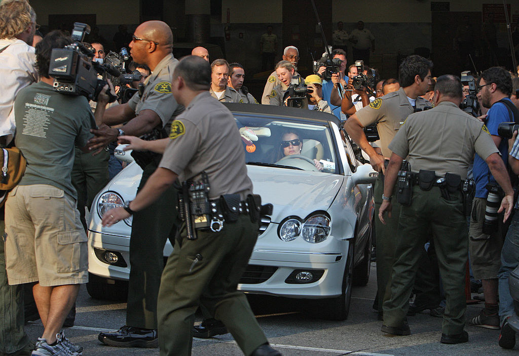 Britney attempting to drive her car as she swarmed by paparazzi and police officers trying to clear the way