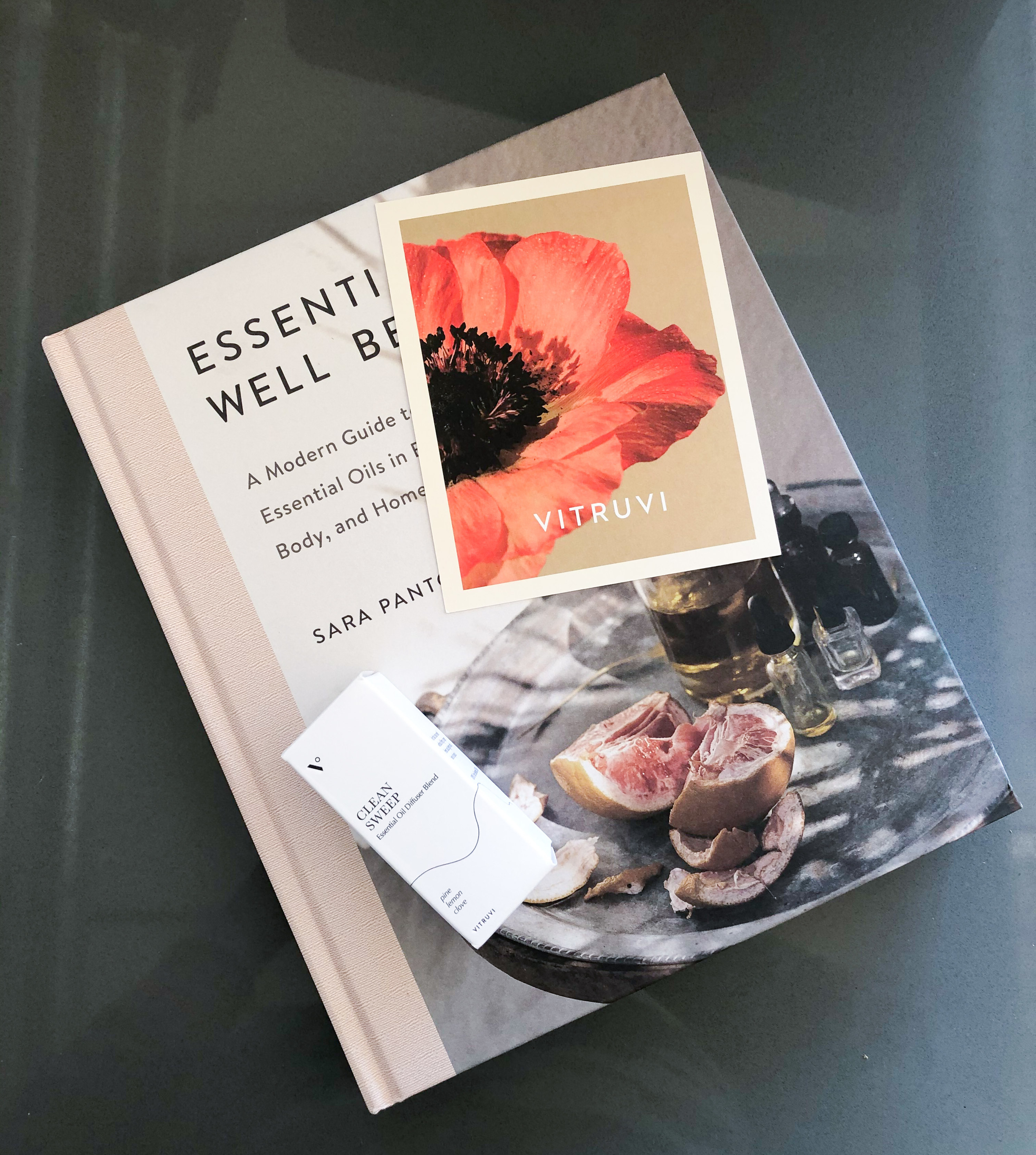 A flatlay of the book on a kitchen counter topped with essential oils