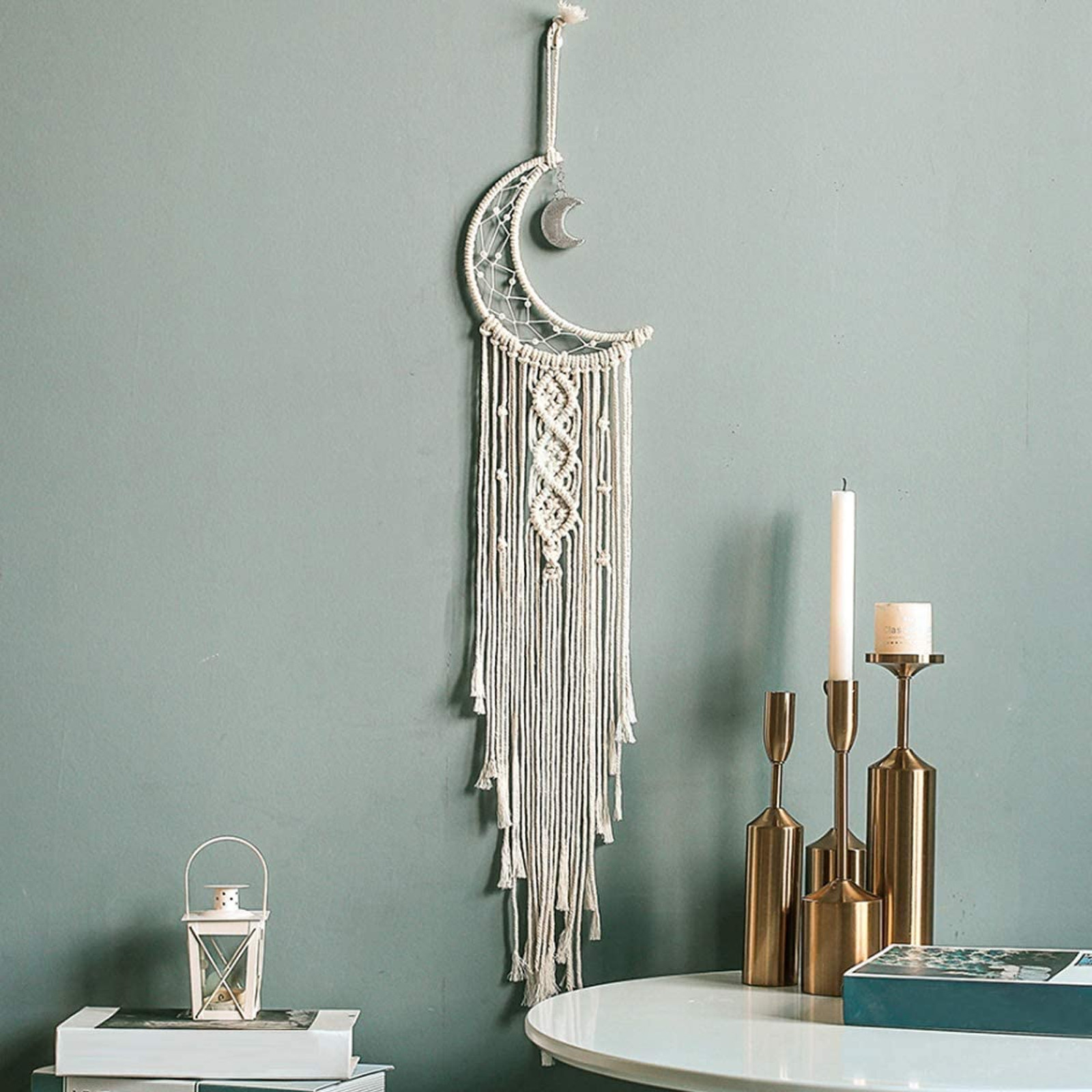 A crescent moon macrame tapestry with tassels and a moon charm