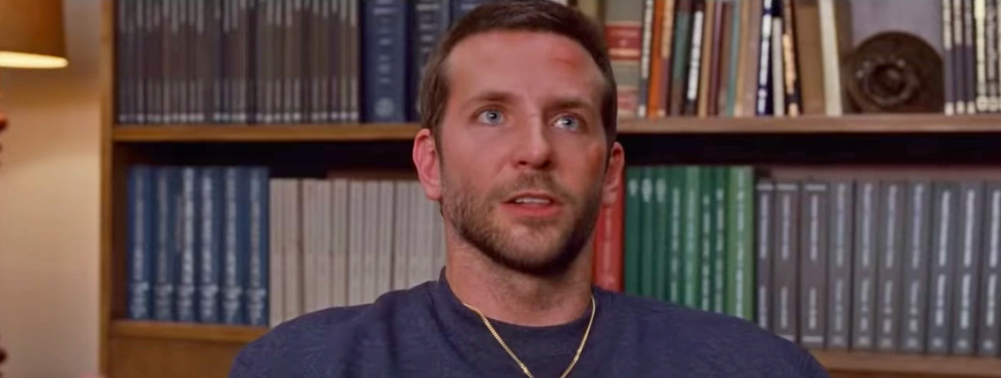 """Bradley Cooper sits in a chair in front of a bookshelf as Pat in """"Silver Linings Playbook"""""""