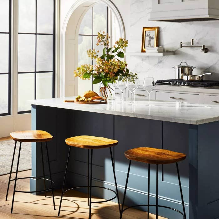Three of the metal and wooden stools in front of a kitchen island