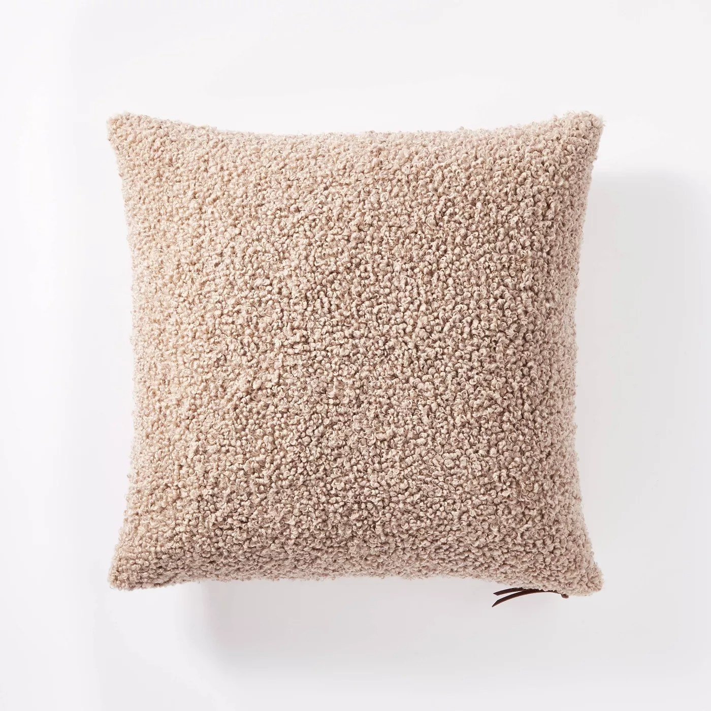 The beige pillow with a leather zipper accent