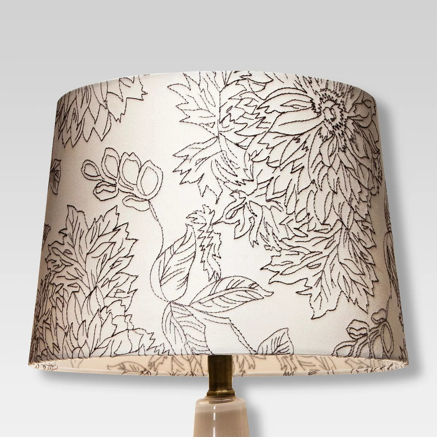 The white lampshade with a black floral pattern stitched into it
