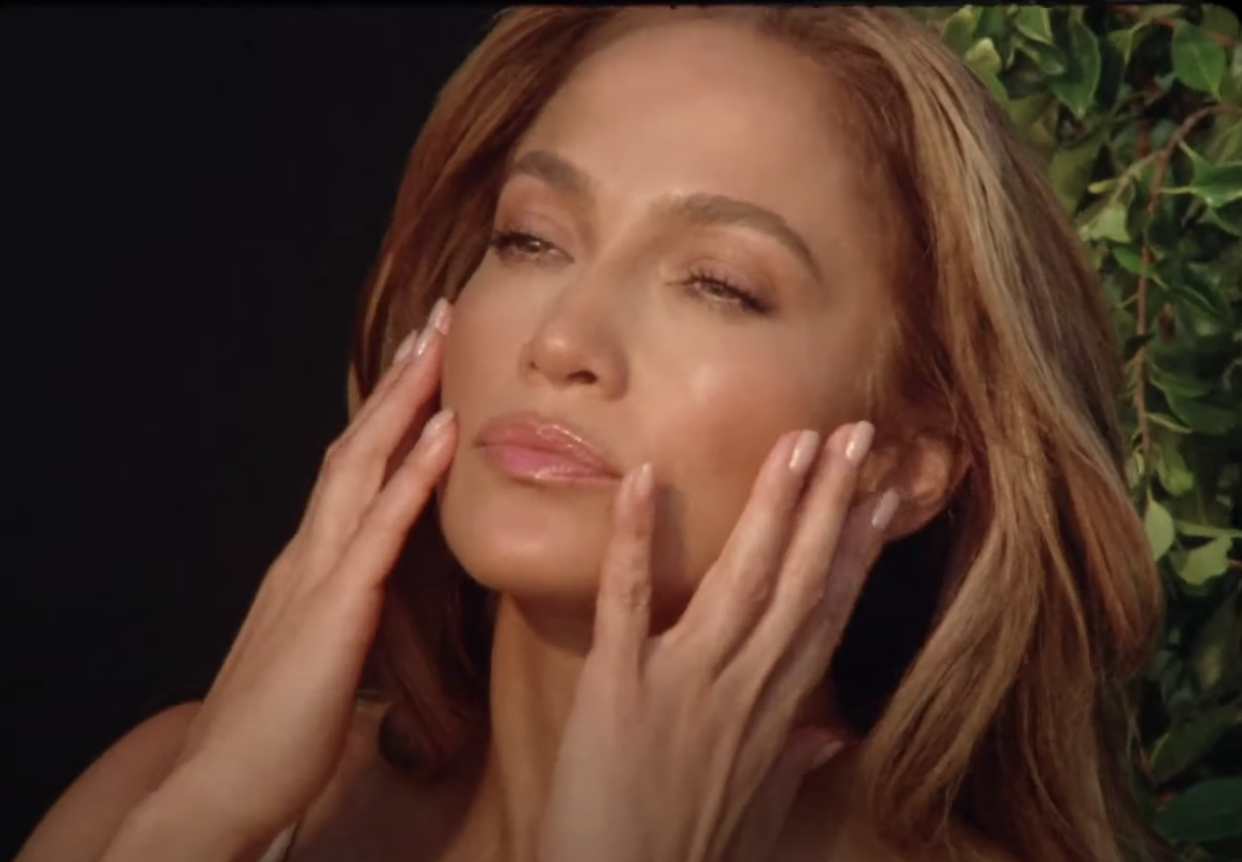 J.Lo touching her face in a skincare commercial