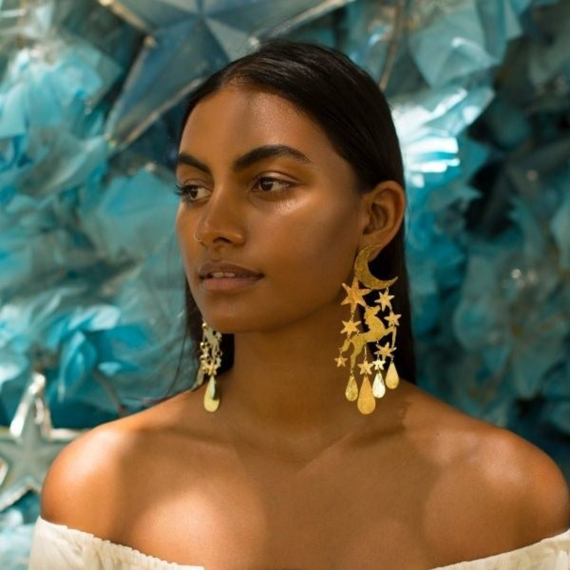 model wearing the large gold earrings that graze their shoulder